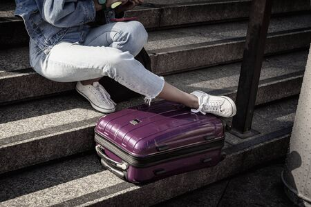 Unrecognizable young girl student sitting resting on the steps with a suitcase, youth travel and tourism concept Reklamní fotografie