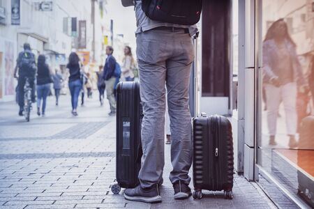 Unrecognizable young man traveling with suitcases, city street, travel and tourism concept