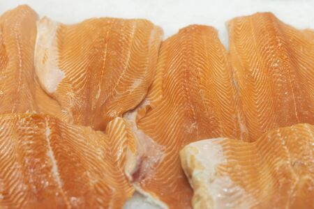 Fillet of salmon to portions close-up on ice in supermarket. Sale of seafood, fish. Open showcases , counter of seafood market Фото со стока