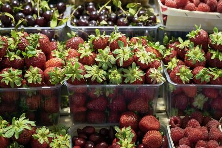 Bright fresh strawberries, raspberries, cherries, fruits and berries. Farmers market with vegetables and fruits, open shelves of shop windows. Healthy organic food, harvest