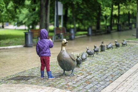 Unrecognizable little girl with her back to us counts the number of little ducklings of mothers duck, sculpture in the park