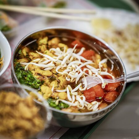 Asian food, spicy soup with vegetables, seafood and germinated soybean sprouts in a bowl close-up, top view. Selective focus