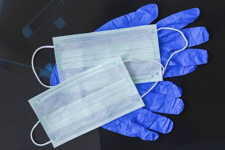 Protective gloves and disposable medical masks on a dark background x-rays photographs. Healthcare concept, quarantine and personal protection