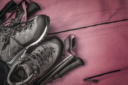 Trekking boots and hiking poles sticks on red background of sports clothing, copy space