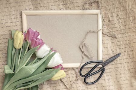 Flat lay of flowers tulips close-up on a wooden frame, vintage background, florist scissors, minimalism. Concept of spring holidays Imagens