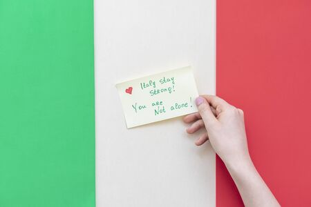 Words of support and solidarity with the people of Italy against the backdrop of the national Italian flag. Concept of attention about COVID-19 and quarantine Imagens