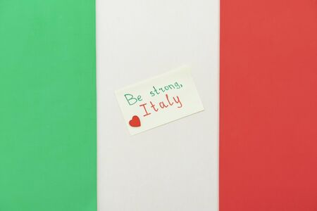 Note with a symbolic heart and the words of support against the backdrop of the national Italian flag. Concept of support and solidarity with people of Italy