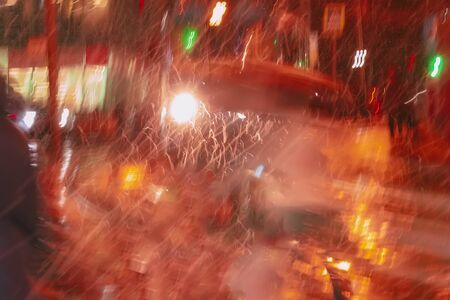 Abstract blurred city background at night, rainy late evening, sparkling glare, illumination and reflections of lights