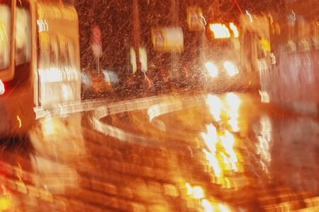 Golden abstract blurred city background at night, rainy late evening, many tram rails, sparkling glare Imagens