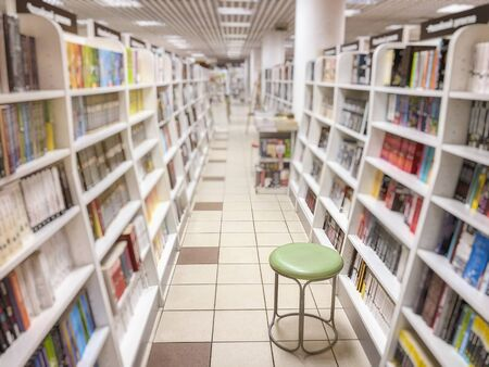 Blurred bookshelves in book store or in library. Empty chair for readers. Education concept, reading fiction, knowledge, life style Imagens