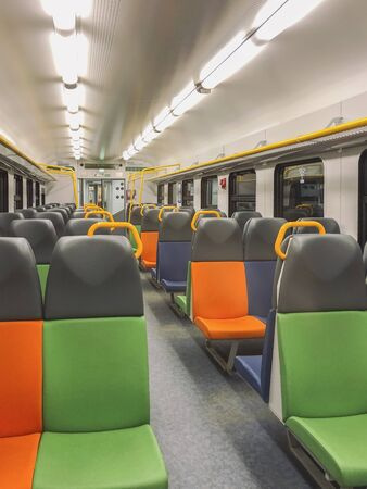 Perspective of an empty train carriage with bright multi-colored passenger seats, rows of chairs