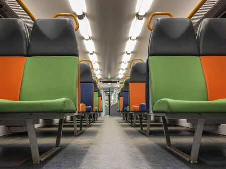 Interior of a modern train, perspective of an empty carriage with bright multi-colored seats
