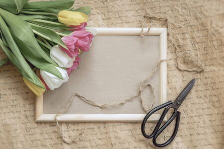 Top view of flowers tulips close-up on a wooden frame, vintage background, florist scissors, minimalism. Concept of spring holidays and gifts