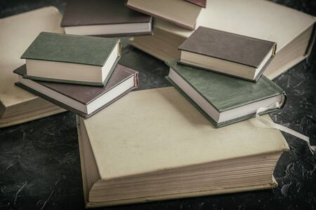 Several different sizes of books close up on a dark background. Concept of back to school, education, reading time Imagens