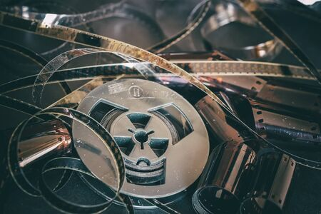 Old coil with 8 mm of film on vintage dark background of cinema strips, photographic films, retro style. Photo, movie, cinema concept