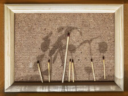 Wooden frame with applique of matches and shadows from young ascending sprouts closeup. Natural picture, nature painting, impressionism.