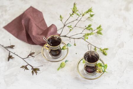 Transparent glass cups with fruit tea, napkin and spring tender tree branches on light background, top view Imagens
