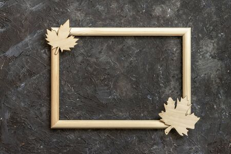 Wooden frame and cutted wooden maple leaves on a dark wall background. Fall, autumn vacation concept. Flat lay, top view, copy space