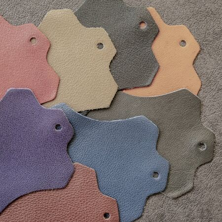 Set of colorful leather samples on dark leather, abstract square background, choice of colors, shades color. Top view Imagens