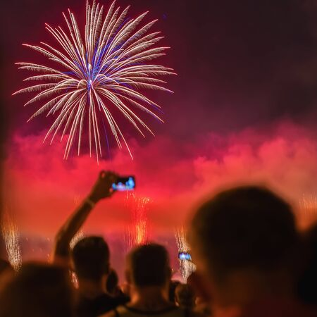 Abstract blurred silhouettes of unrecognizable people back to us watche the fireworks, take photo, celebrate holiday