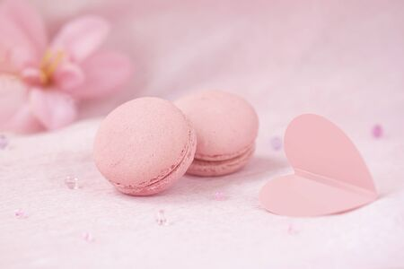 Pair of pink macaroons closeup, heart and flowers, romantic delicate pastel background. Concept of love, greetings. Selective focus Imagens