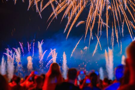 Abstract bright blurred background of silhouettes of unrecognizable people back to us celebrate holiday, watching and admiring firework Imagens