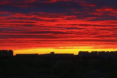Bright red fiery sunset over the dark silhouettes of houses, sky in the clouds, multi-colored paints . Imagens
