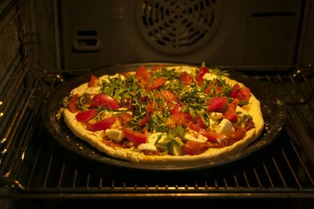 Homemade pizza with fresh tomatoes, mozzarella and arugula in oven, open door, dark background, selective focus, Italian food, real lifestile
