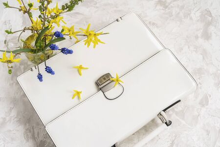 Lying white leather briefcase next to a bouquet of bright flowers, top view. Concept of a spring or summer shopping, business and romance, back to school, mother holiday
