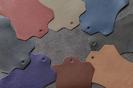 Multicolored leather samples on dark leather, abstract background, texture, choice of colors, shades color. Top view