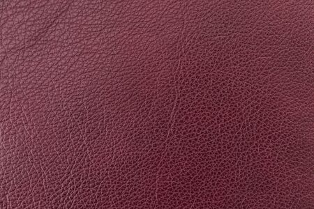 Texture of genuine leather, dark burgundy color, background, surface, pattern for bright backdrop. Manufacturing and leather industry concept