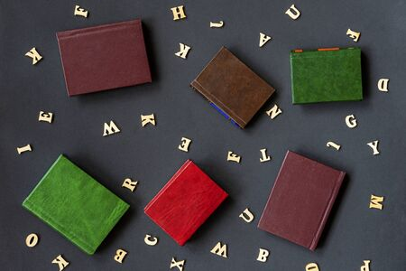 Several books and letters of the English alphabet on a dark background. Education, school, study, reading concept.
