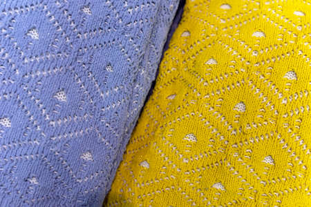 Yellow and blue knitted woolen pullovers, openwork pattern, knitted clothing, texture