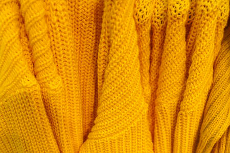 Several knitted warm yellow pullovers with different patterns weigh on a hanger, soft winter background.
