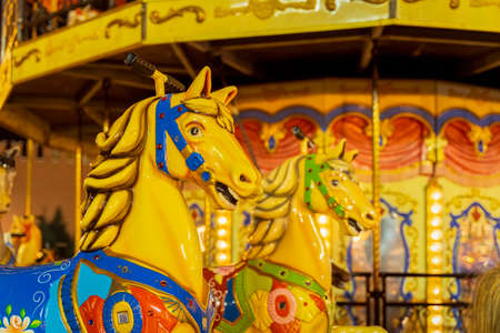 Colourful fairground carousel with bright colorful Horses closeup, city holiday, Christmas market, selective focus