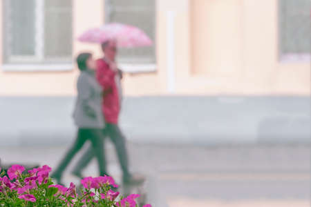 Walking happy couple together, city street in rainy day. Concept of modern city, love, lifestyle. Abstract blurred background