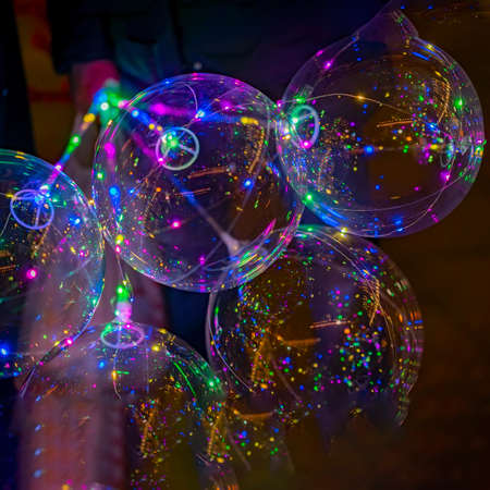 Colorful LED balloons on the black background. Multicolored vivid glowing bokeh lights at night.