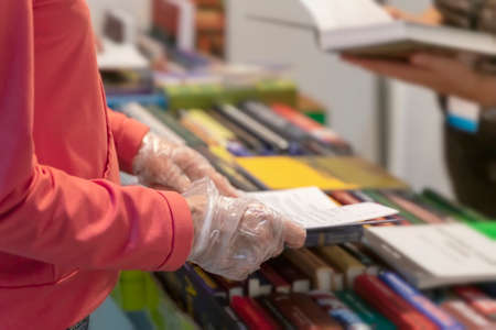 Abstract person in disposable protective gloves with book in hands, library, bookstore. New normal. Risk area for spreading infection. Healthcare concept. Selective blured focus. Standard-Bild