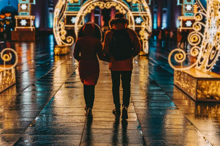 Two unrecognizable enamored young people going in neon lighting arch, city with festive illumination. Late evening, Christmas, holidays. Romantic date concept