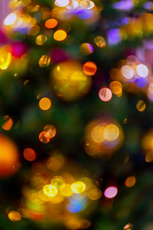 Abstract blurred festive background for design. Christmas tree with decorations, christmas balls, lighted garlands, bokeh. Winter holiday, Happy New Year, xmas.