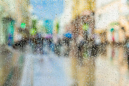 View through window with droplets. Blurred modern city, defocused urban bokeh city, silhouettes of the walking people, shop windows. Bright abstract colorful background