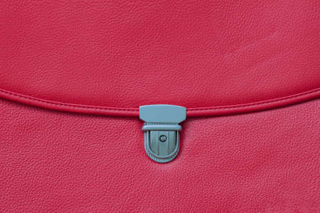 Fashionable red bag from genuine leather close-up, texture.Detail of leather briefcase, metal clasp, background, copy space