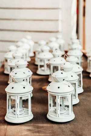 Old white lanterns with candles inside on wooden table. Preparing for Christmas, cozy decor Standard-Bild