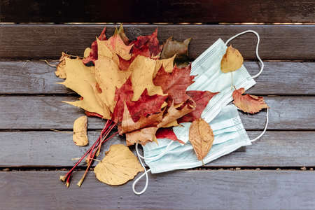 Bouquet of maple leaves and medical disposable masks on a wooden park bench. Healthcare and coronavirus concept, quarantine, personal protection. New normality Standard-Bild