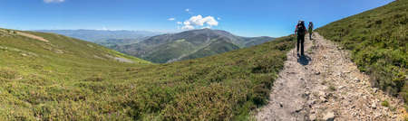Travelers with a backpacks and trekking sticks, bumpy rocky road in the mountains, blue sky with high clouds. Active and healthy lifestyle in summer
