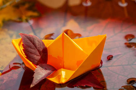 Origami yellow paper boat in a rain puddle between fallen autumn leaves, water circles, fall weather and mood