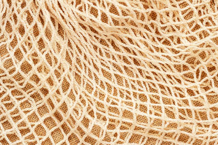 Texture of beige mesh string reusable knitted bag. Concept of zero waste, recycling, ecology.