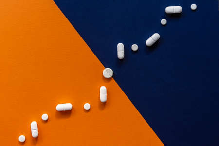 Colorful blue orange background with white pills in the form graph. Medical concept of a health, pharmacy and healthcare Standard-Bild