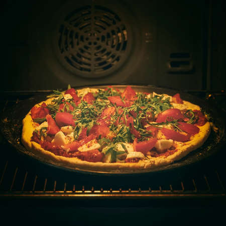 Baking pizza in home oven. Dark food background. Home cooking. Delicious pizza with fresh ingredients, tomatoes, arugula and cheese Standard-Bild
