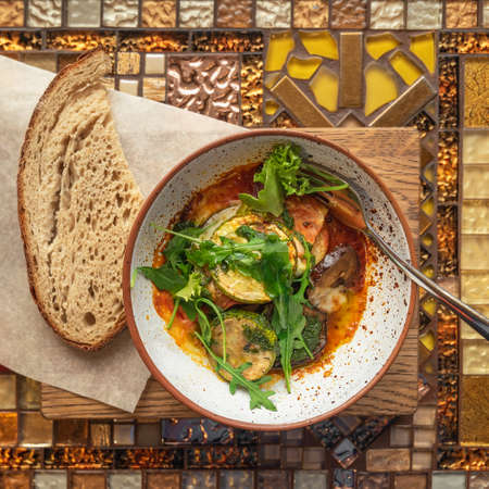 Bowl of baked eggplant, tomatoes, arugula leaves and spices. Piece of black bread. Healthy vegetable. Diet menu. Top view Standard-Bild
